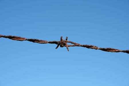 Rusty Barbed Wire against a blue sky Stock Photo - 1835023