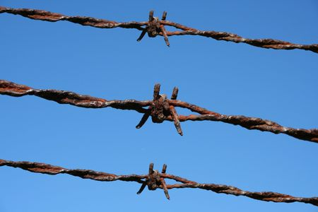 Rusty Barbed Wire against a blue sky Stock Photo - 1857782