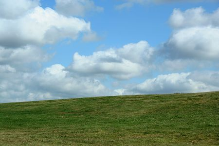A Green Field and cloudy blue sky Imagens