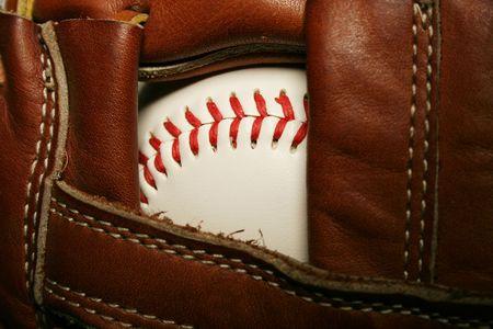 A close up of a Baseball in a glove photo