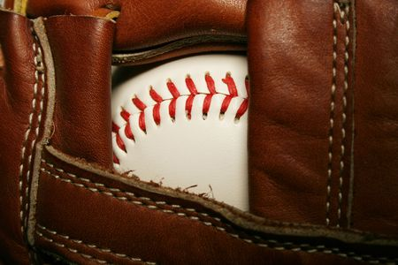 A close up of a Baseball in a glove