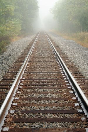 霧の日に木がある鉄道の線路