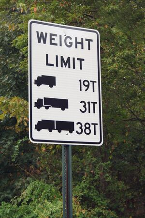A Truck Weight Limit Sign against trees