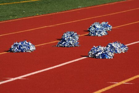 Cheerleader pom poms near a football field Stock Photo