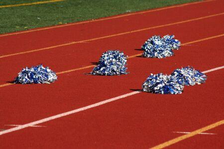 Cheerleader pom poms near a football field Imagens