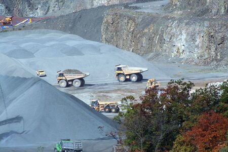 A Rock Quarry with equipment and trucks