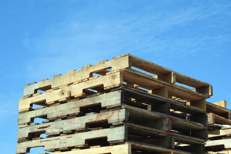 delivery room: Stacked Pallets against a blue sky Stock Photo