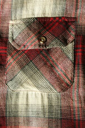 flannel: A close up of a Red flannel shirt pocket