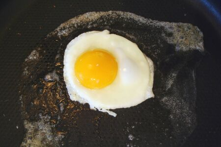 sunnyside: A Sunnyside up egg frying in a pan Stock Photo