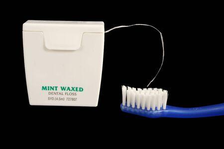 Hilo dental y cepillo de dientes sobre fondo negro