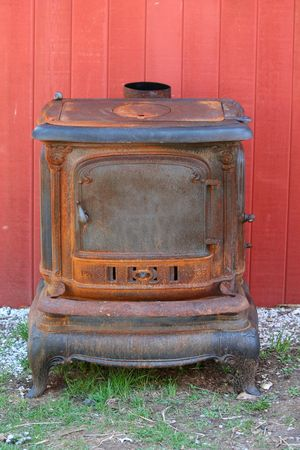 A Old rusty cast iron stove next to a barn