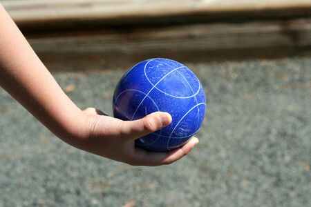 A Hand holding a blue bocce ball