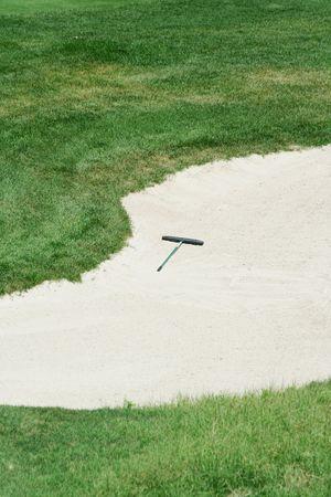 Golf rake in a sand trap Reklamní fotografie