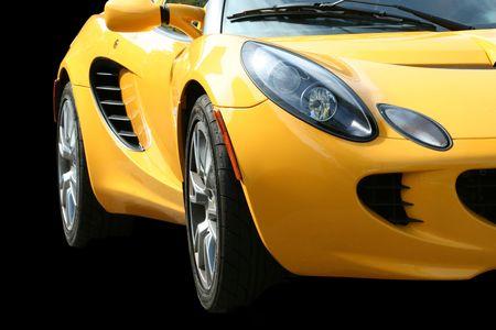 黒の上の孤立した黄色スポーツ車 報道画像