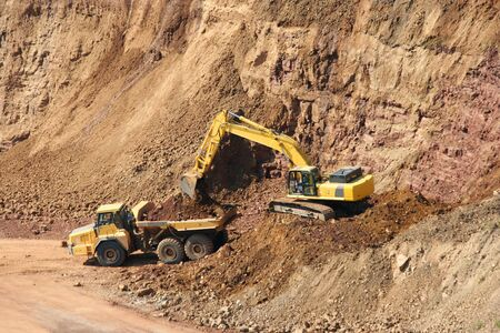 A Backhoe and dumptruck at rock quarry photo