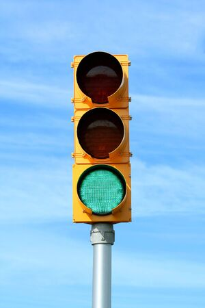 Green traffic signal light against blue sky Stock Photo
