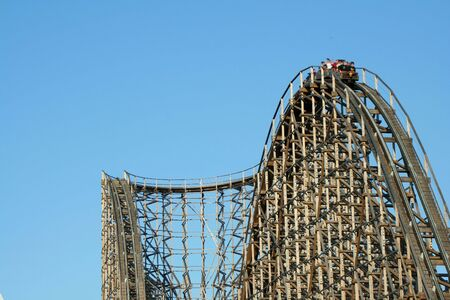 Wooden roller coaster support beams against blue sky