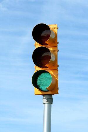 Green traffic signal light against blue sky photo