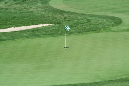 A green flag on a golf green Stock Photo