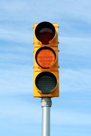 青い空を背景に明るい黄色の交通信号 写真素材