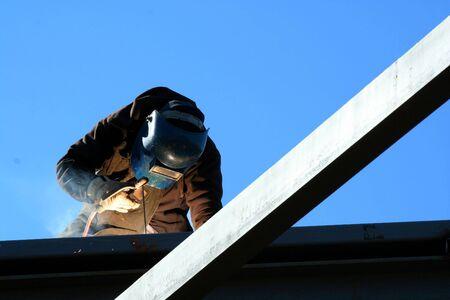 Een lasser op het dak van een bouwplaats
