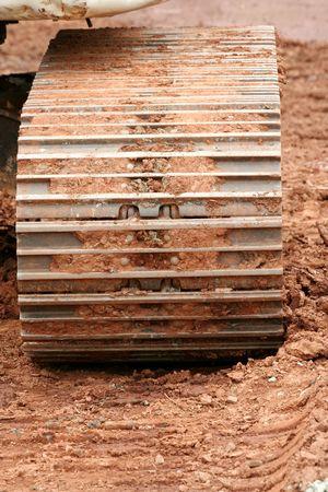 muddy tracks: Muddy caterpillar tracks on a backhoe