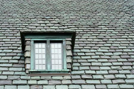 Een oud dak in leisteen met venster