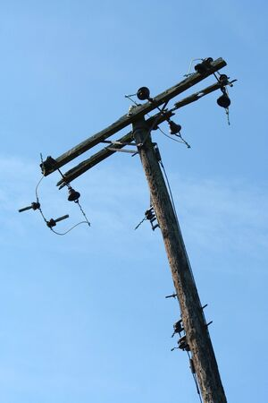 A old telephone pole against blue sky