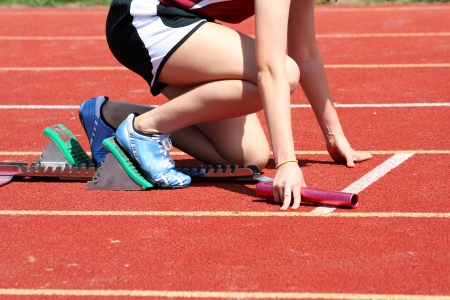 Runner in the starting blocks with baton Stock Photo - 4848262