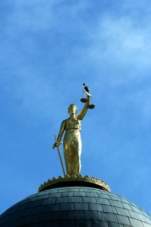 A Lady Justice statue against blue sky