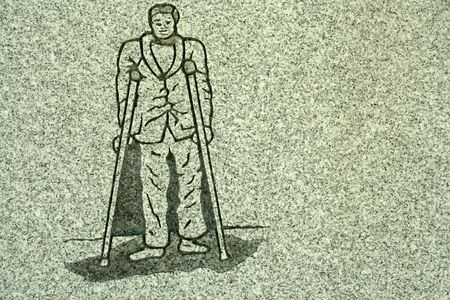 a Stone carving of a man on crutches