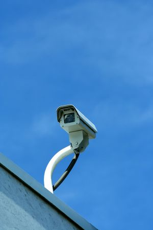 A Security camera against blue sky photo