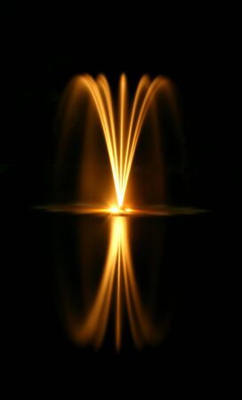 A water fountain at night with reflection