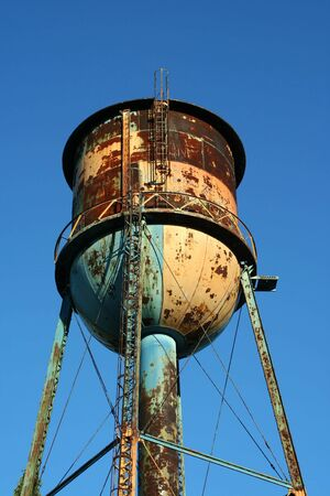 A Old rusty watertower against blue sky photo