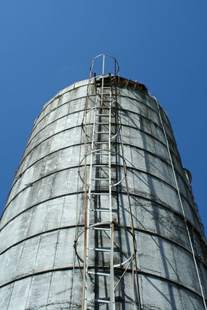 Looking up a grain silo with blue sky photo