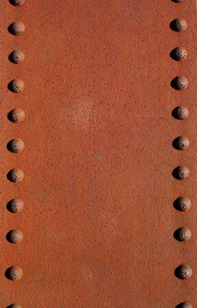 A Rusty metal plate with rivets photo