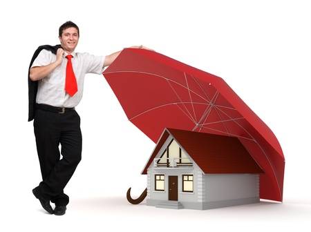 weather protection: Young businessman standing near a house protected by a red umbrella - House insurance Concept Stock Photo