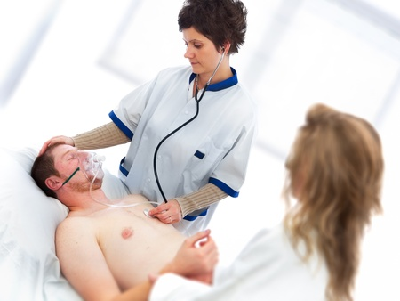 oxygen: Young man being checked by a doctor for vital signs