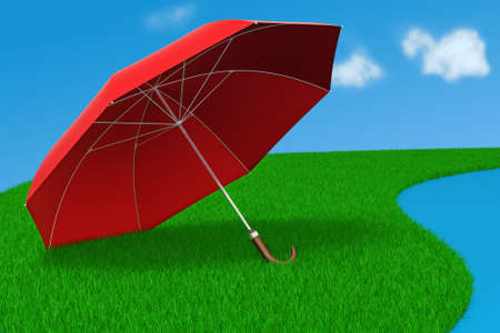 Red umbrella in the grass near water in the sunshine photo
