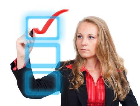 Young business woman drawing a virtual check mark on a virtual monitor photo