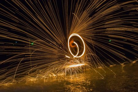 steel wool: Burning steel wool spinned in urban area. Showers of glowing sparks from spinning steel wool Stock Photo