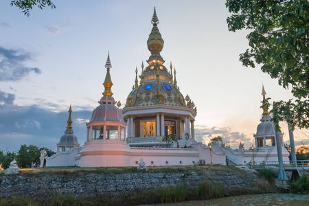 thee: Wat Thung Saet Thee Beautiful modern pagoda reflection with water during sunset twilight time at Khon Kaen, Thailand. Stock Photo