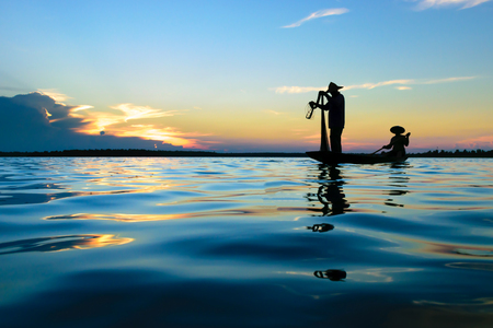 asian fisherman silhouette fishing on the both during sunset. Stock Photo