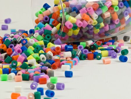 Brightly coloured beads spilling out of glass Stock Photo - 4531617