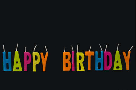 Coloured wax candles saying Happy Birthday on black