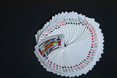 Full pack of playing cards on black  Editorial