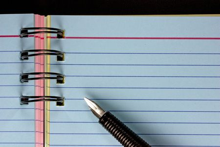 Fountain pen poised over a Blank page in a note pad