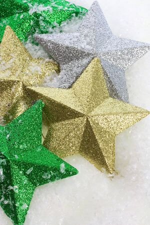 Green ,gold and silver stars on snow