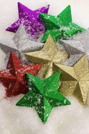 Coloured stars on snow background Stock Photo