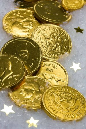 Gold chocolate coins on ice and star background